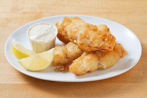 Battered fish fillets with tartar sauce and lemon wedges