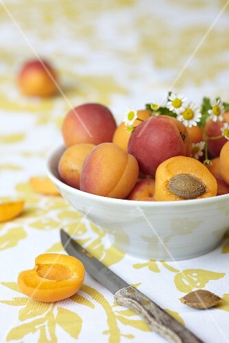 A bowl of apricots, whole and halved