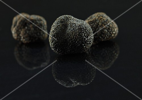 Black truffles on a black surface