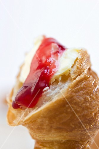 A croissant with butter and strawberry jam (close-up)