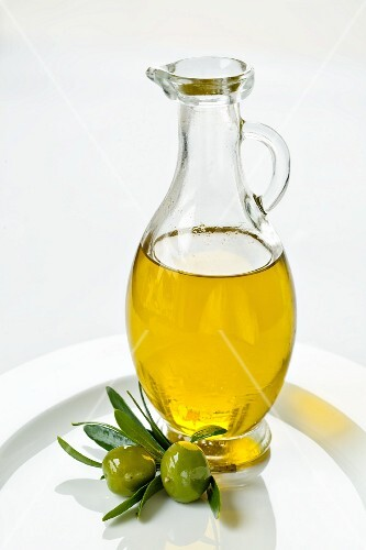 A carafe of olive oil and green olives