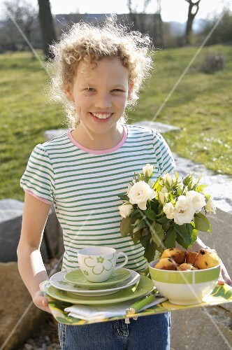 Curly-haired girl carrying tray for breakfast out of doors