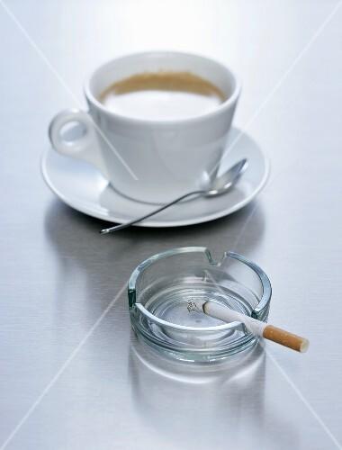 eine tasse kaffee mit einer zigarette im aschenbecher. Black Bedroom Furniture Sets. Home Design Ideas