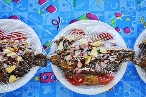 Sweet-sour tilapia on plates covered with clingfilm