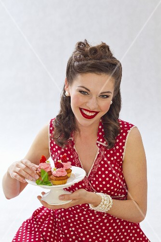 A retro-style girl holding a plate of strawberry muffins