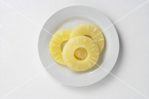 Three pineapple slices on a plate, seen from above