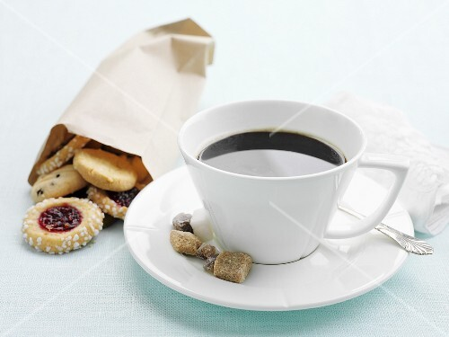 A cup of coffee with sugar and a bag of biscuits