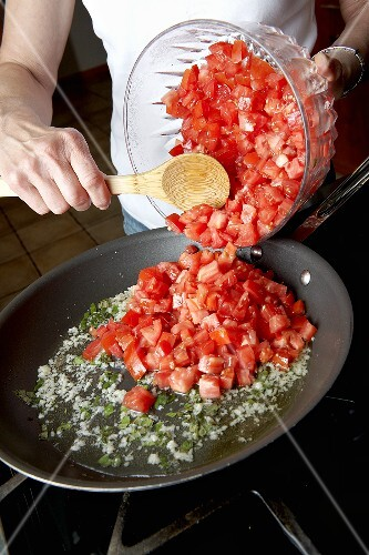 Woman Adding Fresh Diced Tomatoes into a Skillet on the Stove