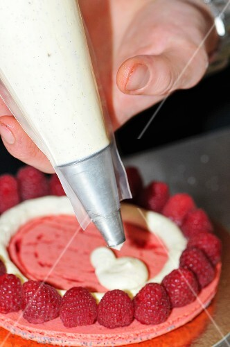 A raspberry cake being decorated with vanilla cream