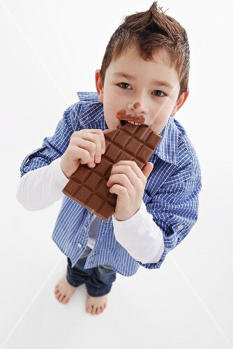 A little boy eating a bar of chocolate