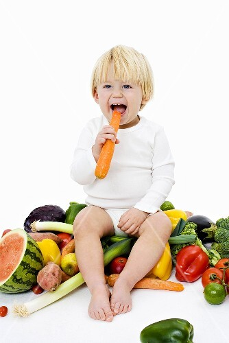 Little child sitting on a pile of vegetables