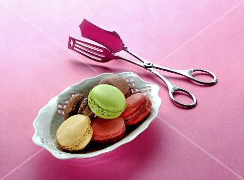 Different types of macaroons in a porcelain dish with a pair of tongs next to it