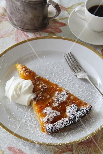 A slice of peach tart with icing sugar and cream