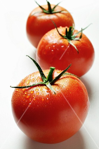 Three tomatoes with drops of water