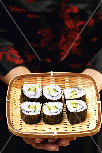 Asian woman holding maki-sushi on wicker tray