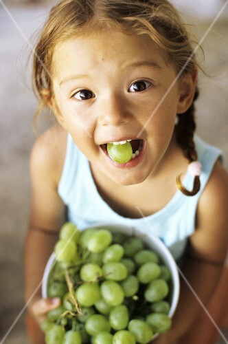 Girl with grape in her mouth