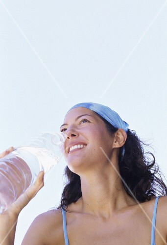 Young woman drinking mineral water in the open air