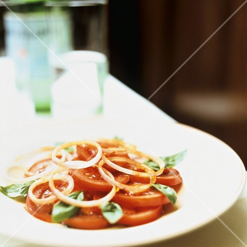 Tomato salad with onion rings and basil