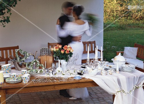 Wedding table with gifts, bride and groom dancing