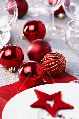 Red Christmas baubles on laid table