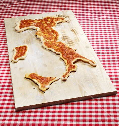 Pizza in the shape of the map of Italy on chopping board