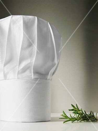 A chef's hat, rosemary beside it