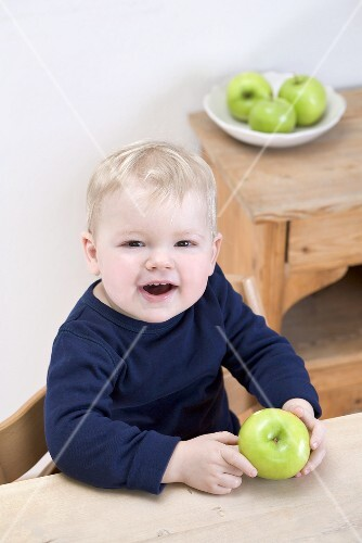 Small boy with a Granny Smith apple