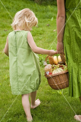 Little girl carrying a picnic basket with her mother