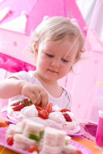 Little girl taking strawberry from pavlova