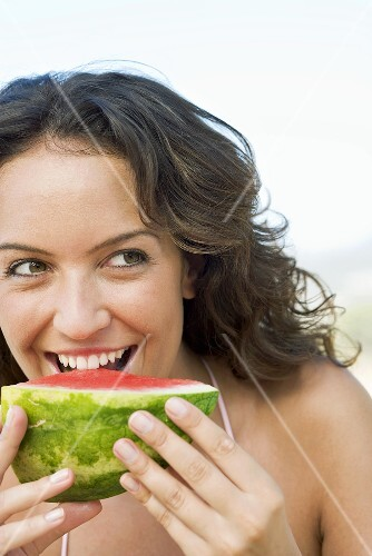 Woman eating a piece of watermelon