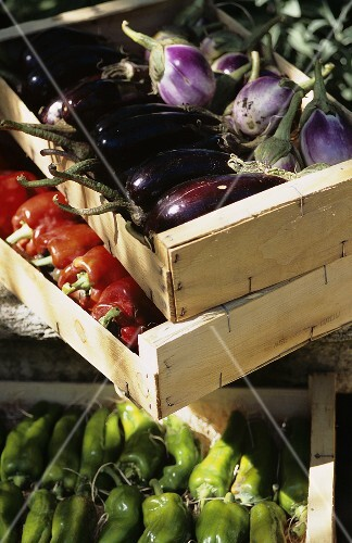 Fresh aubergines and peppers in wooden boxes