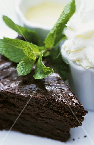 A piece of chocolate cake, fresh mint, whipped cream