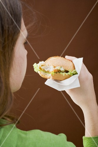 Girl eating a breaded escalope in a bread roll