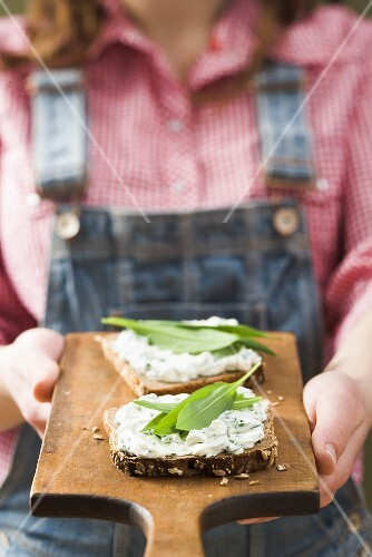 Person holding wholemeal bread with quark &amp; ramsons on board