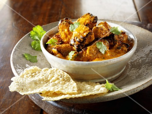 Curry with coriander leaves and poppadoms