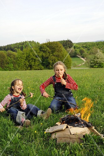 Two girls grilling sausages over a camp-fire