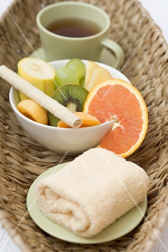 Cup of tea, fresh fruit and towel in basket