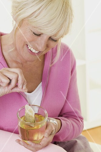 Woman putting tea bag into cup of hot water
