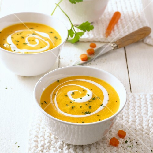 Two bowls of carrot soup with swirls of cream