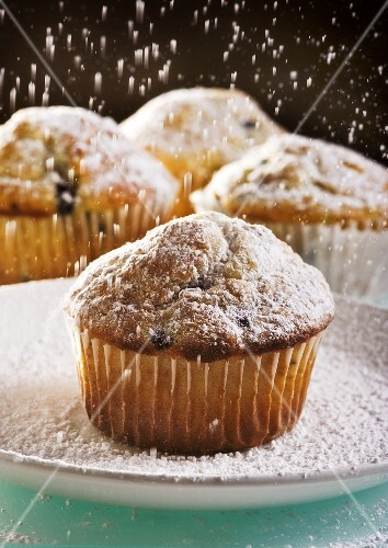 Blueberry Muffins Being Dusted with Powdered Sugar