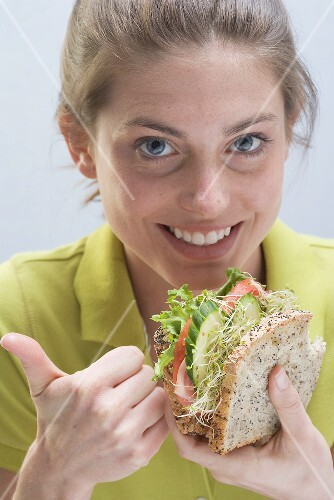 Smiling woman with sandwich