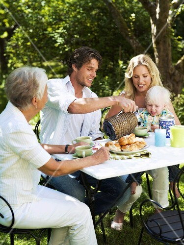 Family drinking coffee in the garden in summer
