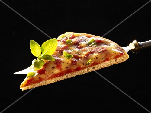 A slice of pizza Margherita with basil on knife