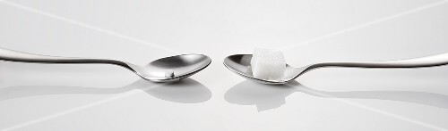 Two spoons, one with a sweetener, one with a sugar cube