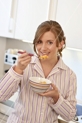 Young woman eating a bowl of cornflakes