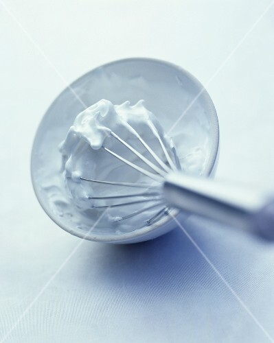 Beaten egg white in bowl with whisk