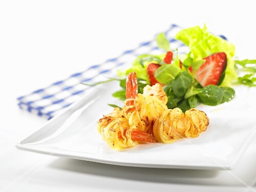 Prawns wrapped in potato on a spring salad with a white balsamic dressing
