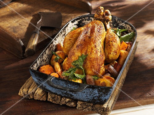 Roast chicken with root vegetables in an old roasting pan