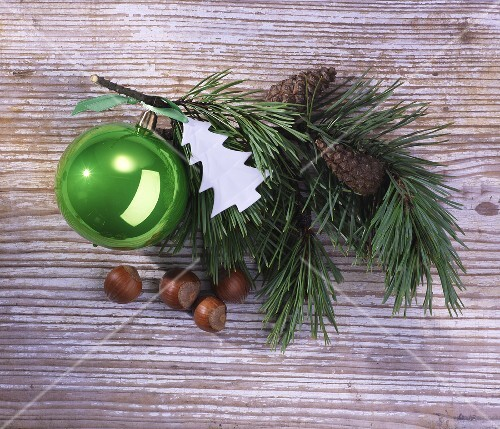 A sprig of pine with Christmas decoration on a wooden surface