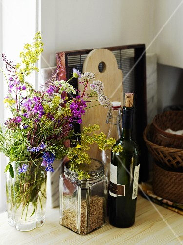 Vases with flowers, red wine bottle and kitchen implements